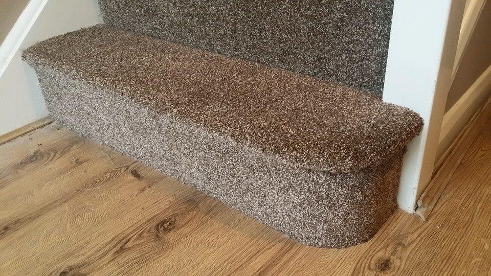 a carpeted stair and woodgrain vinyl floor